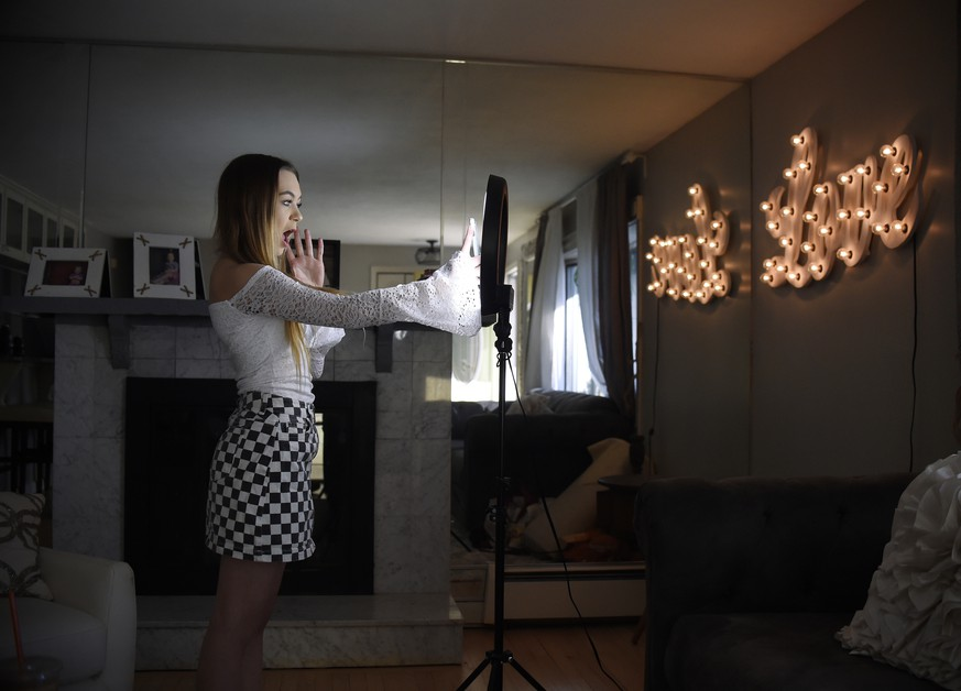 In this Feb. 28, 2018 photo, Matty Nev Luby holds up her phone in front of a ring light she uses to lip-sync with the smartphone app Musical.ly, in Wethersfield, Conn. Teens and young adults say cyberbullying is a serious problem for people their age, but most don't think they'll be the ones targeted for digital abuse. The high school gymnast's popularity on the lip-syncing app Musical.ly, which merged this summer into the Chinese video-sharing app TikTok, helped win her some modeling contracts. Luby said she's learned to navigate Instagram and other social media apps by brushing aside the anonymous bullies. (AP Photo/Jessica Hill)