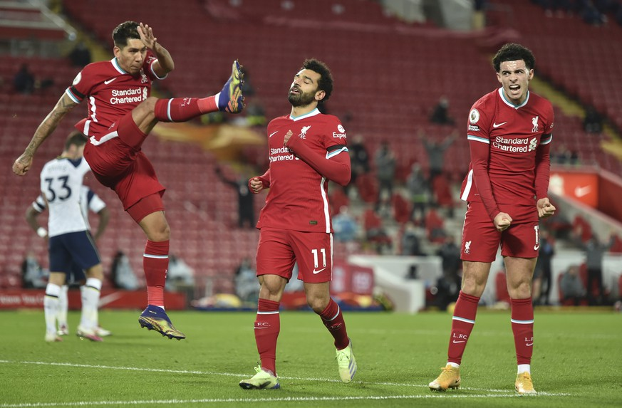 Liverpool's Mohamed Salah, center celebrates with teammates Liverpool's Roberto Firmino, left and Liverpool's Curtis Jones after scoring the opening goal of the game during their English Premier League soccer match between Liverpool and Tottenham Hotspur at Anfield in Liverpool, England, Wednesday, Dec., 16, 2020. (Peter Powell/ Pool via AP)