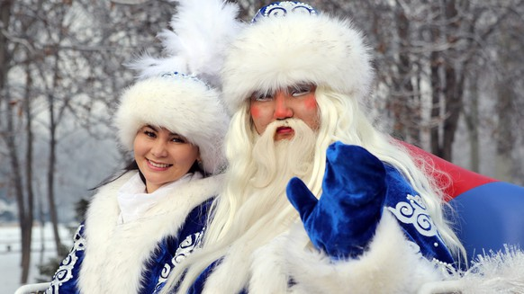epa05692390 A man and a woman dressed as Father Frost (R) and his granddaughter (L) take part in a New Year's Eve celebration in Bishkek, Kyrgyzstan, 31 December 2016. Father Frost is the Slavic culture equivalent of Santa Claus.  EPA/IGOR KOVALENKO
