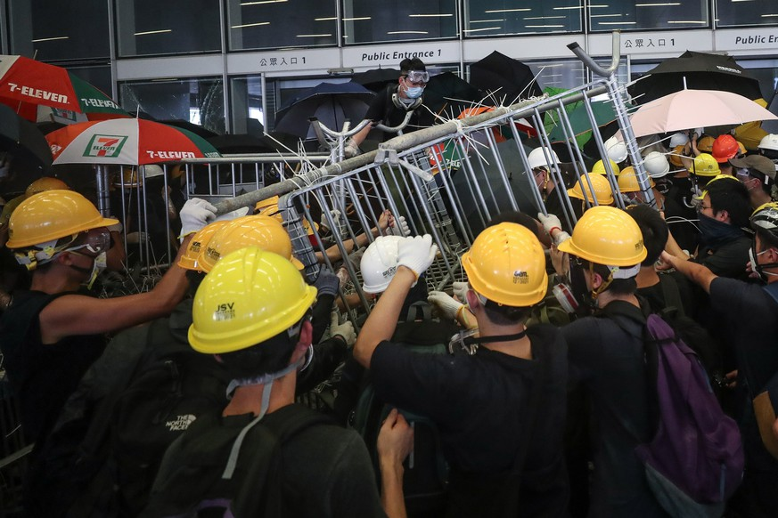 epa07686882 Protesters try to break into the Legislative Council building during the annual 01 July pro-democracy march in Hong Kong, China, 01 July 2019. Protesters are demanding the resignation of Hong Kong Chief Executive Carrie Lam and the full withdrawal of a suspended extradition bill. On 01 July, Hong Kong marks the 1997 transfer of sovereignty of Hong Kong from Britain to China.  EPA/RITCHIE B. TONGO