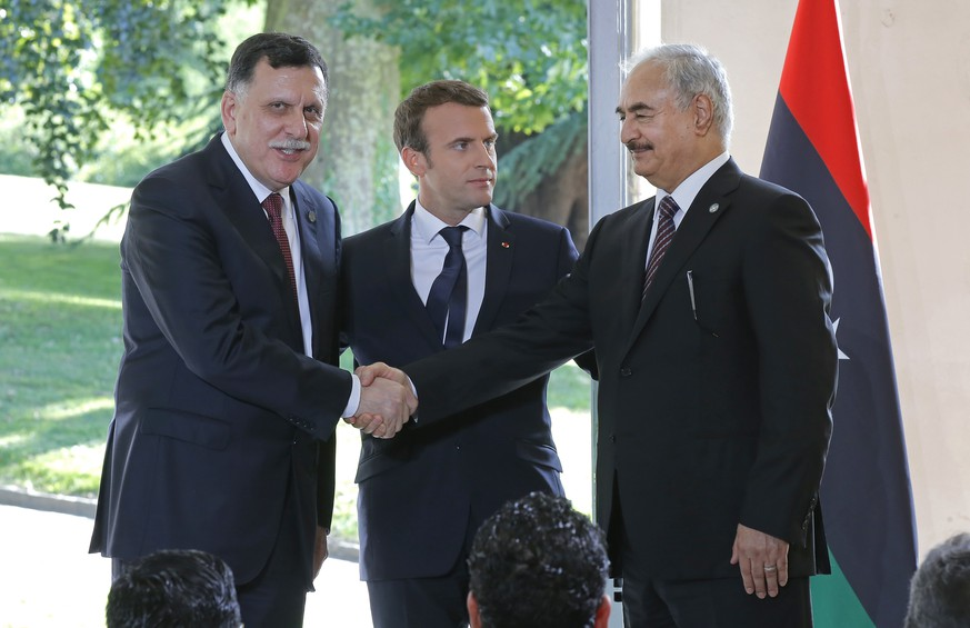 Libya's Prime Minister Fayez al-Sarraj of the U.N.-backed government, left, and General Khalifa Hifter of the Egyptian-backed commander of Libya's self-styled national army shake hands as France's President Emmanuel Macron stands between after a declaration at the Chateau of the La Celle-Saint-Cloud, west of Paris, France, Tuesday, July 25, 2017. President Emmanuel Macron is hosting a meeting of the two main rival leaders of chaotic Libya, trying to play peacemaker in a country where the stakes are high for both Europe and Africa. (AP Photo/Michel Euler)