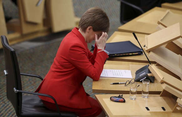 Scotland's First Minister Nicola Sturgeon reacts at the Scottish Parliament in Edinburgh, Scotland, Tuesday Dec. 22, 2020, where she gives an update on COVID-19 restrictions. Scotland has imposed some increased restrictions for the Christmas season. (Russell Cheyne/PA via AP)