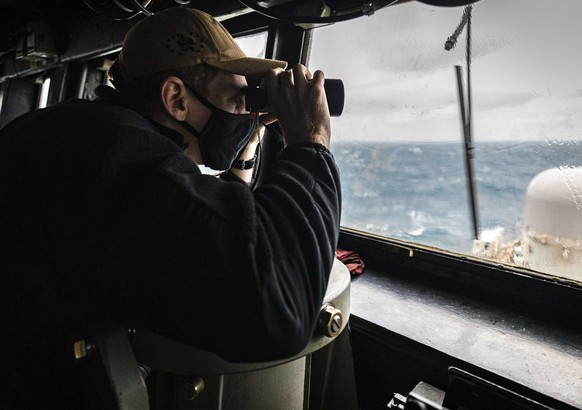 In this photo provided by U.S. Navy, Ensign Grayson Sigler, from Corpus Christi, TX., scans the horizon while standing watch in the pilot house as guided-missile destroyer USS John S. McCain conducts routine underway operations in support of stability and security for a free and open Indo-Pacific, at the Taiwan Strait, Wednesday, Dec. 30, 2020. China accused the U.S. of staging a show of force by sailing two Navy warships through the Taiwan Strait on Thursday morning. The Navy said the Arleigh Burke-class guided missile destroyers USS John S. McCain and USS Curtis Wilbur