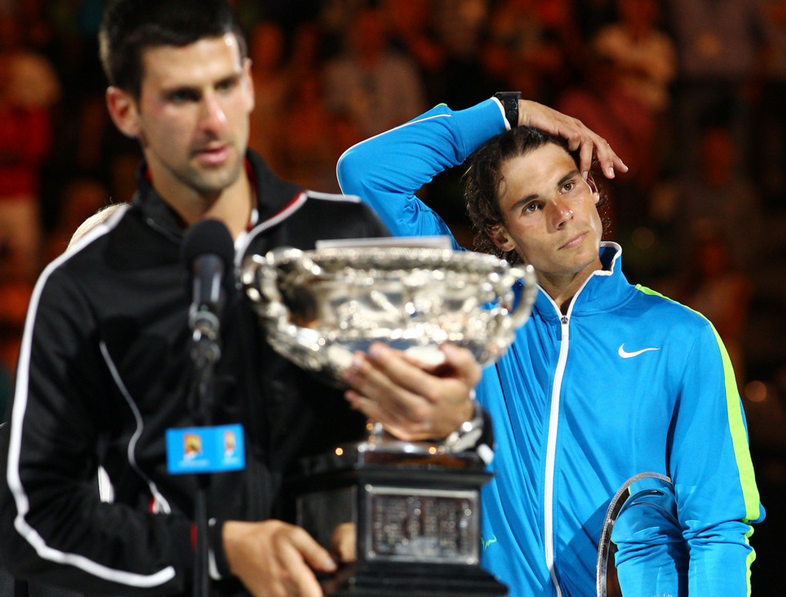 Spain's Rafael Nadal, right, looks on as Serbia's Novak Djokovic addresses the crowd after winning the men's singles final against  at the Australian Open tennis championship, in Melbourne, Australia, early Monday, Jan. 30, 2012. (AP Photo/Rick Rycroft)