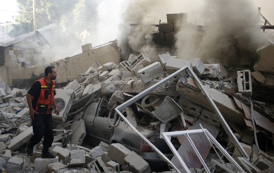 A Palestinian firefighter participates in efforts to put out a fire from the wreckage of a house, which witnesses said was destroyed in an Israeli air strike, in Gaza City July 31, 2014. Israel pressed ahead with its Gaza offensive saying it was days from achieving its core goal of destroying all Islamist guerrilla cross-border attack tunnels, but a soaring Palestinian civilian toll has triggered international alarm. Gaza officials say at least 1,361 Palestinians, most of them civilians, have now been killed in the battered enclave. Israel has lost 56 soldiers to Gaza clashes and three civilians to Palestinian shelling. REUTERS/Mohammed Salem (GAZA - Tags: CIVIL UNREST MILITARY POLITICS CONFLICT)