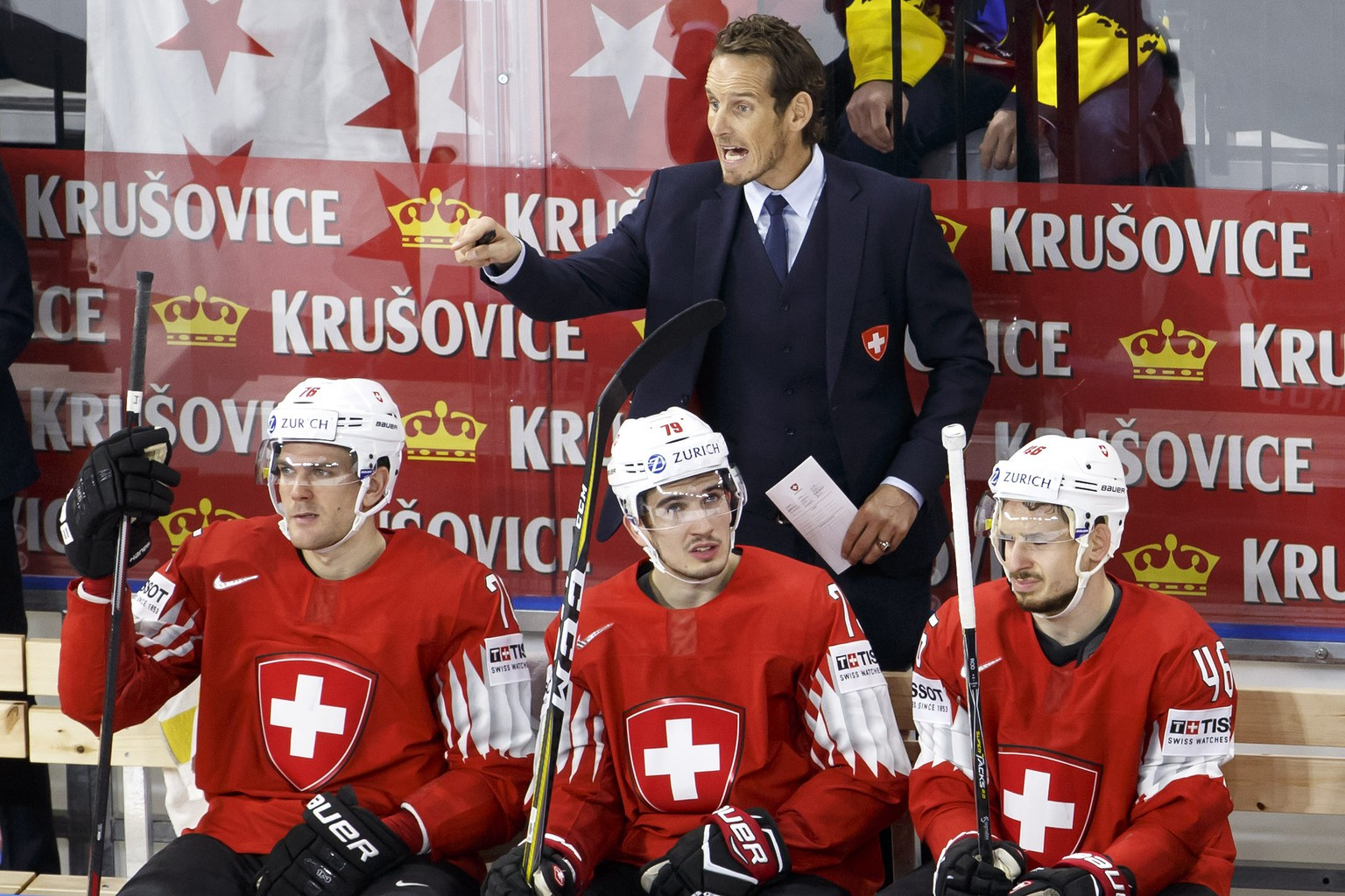 Patrick Fischer, head coach of Switzerland national ice hockey team, gestures behind his players defender Joel Genazzi, left, forward Damien Riat, center, and forward Noah Rod, right, during the IIHF 2018 World Championship preliminary round game between Switzerland and Austria, at the Royal Arena, in Copenhagen, Denmark, Saturday, May 5, 2018. (KEYSTONE/Salvatore Di Nolfi)