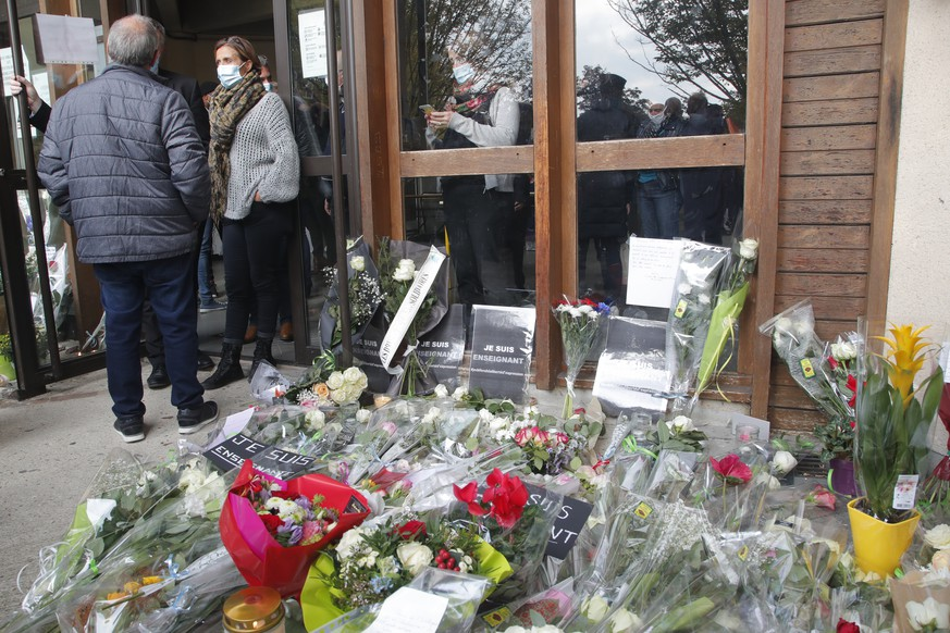 Flowers lay outside the school where slain history teacher Samuel Paty was working, Saturday, Oct. 17, 2020 in Conflans-Sainte-Honorine, northwest of Paris. French President Emmanuel Macron denounced what he called an