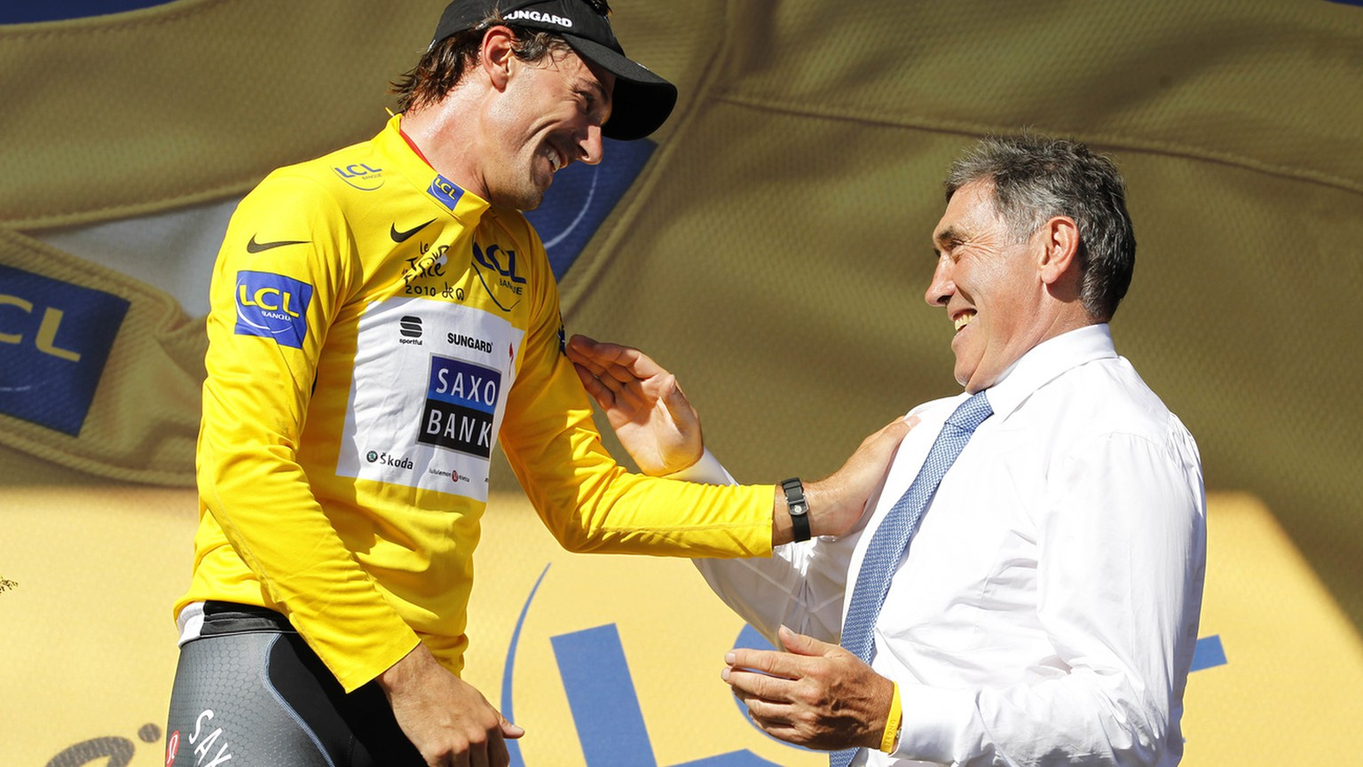 Fabian Cancellara of Switzerland, wearing the overall leader's yellow jersey, left, and Belgium cyclist and Tour de France winner Eddy Merckx, right, react on the podium after the first stage of the Tour de France cycling race over 223,5 kilometers (139 miles) with start in Rotterdam, Netherlands and finish in Brussels, Belgium, Sunday July 4, 2010. (AP Photo/Bas Czerwinski)