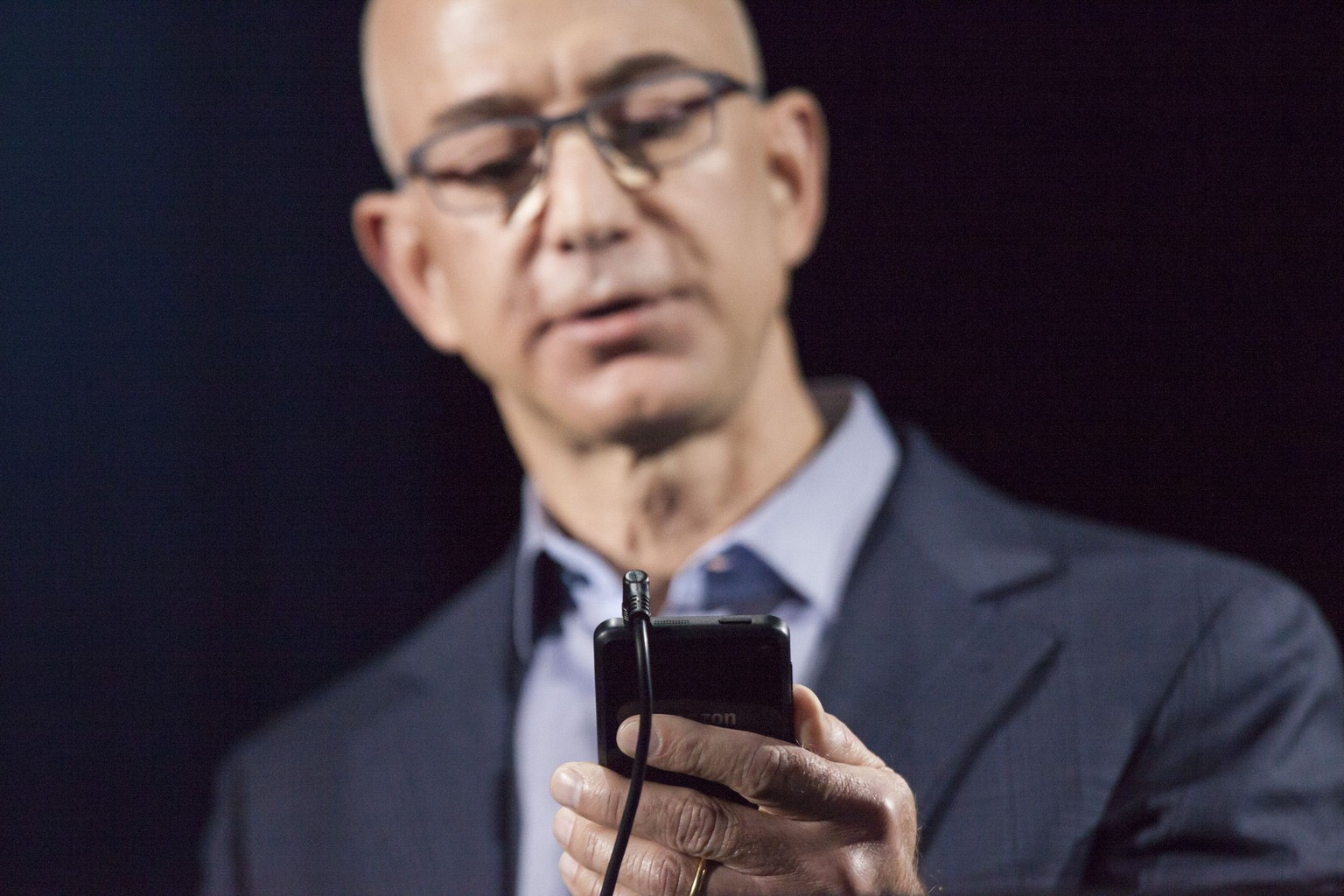 SEATTLE, WA - JUNE 18: Amazon.com founder and CEO Jeff Bezos demonstrates the company's first smartphone, the Fire Phone, on June 18, 2014 in Seattle, Washington. The much-anticipated device is available for pre-order today and is available exclusively with AT&T service.   David Ryder/Getty Images/AFP == FOR NEWSPAPERS, INTERNET, TELCOS & TELEVISION USE ONLY ==
