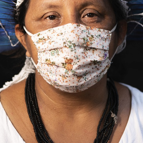 Sonia Vilacio, 46, of the Sateré Mawé indigenous ethnic group, poses for a portrait wearing the traditional dress of her tribe and a face mask amid the spread of the new coronavirus in Manaus, Brazil, Wednesday, May 27, 2020. The new coronavirus has hit S