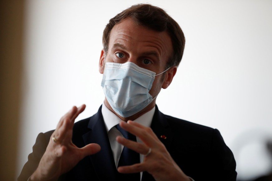 epa08348358 French President Emmanuel Macron, wearing a protective face mask, talks with health workers as he visits a medical center in Pantin near Paris as the spread of the coronavirus disease (COVID-19) continues in France, April 7, 2020.  EPA/GONZALO FUENTES / POOL / POOL  MAXPPP OUT