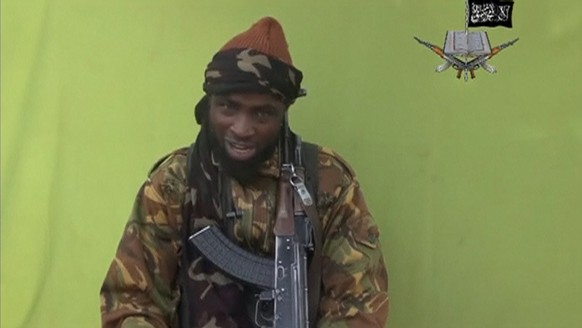 Boko Haram leader Abubakar Shekau speaks at an unknown location in this still image taken from an undated video released by Nigerian Islamist rebel group Boko Haram. The leader of the Nigerian Islamist rebel group Boko Haram has offered to release more than 200 schoolgirls abducted by his fighters last month in exchange for prisoners, according to a video seen on YouTube. About 100 girls wearing full veils and praying are shown in an undisclosed location in the 17-minute video in which Shekau speaks. MANDATORY CREDIT. REUTERS/Boko Haram handout via Reuters TV (CONFLICT POLITICS CRIME LAW) ATTENTION EDITORS - THIS PICTURE WAS PROVIDED BY A THIRD PARTY. REUTERS IS UNABLE TO INDEPENDENTLY VERIFY THE AUTHENTICITY, CONTENT, LOCATION OR DATE OF THIS IMAGE. FOR EDITORIAL USE ONLY. NOT FOR SALE FOR MARKETING OR ADVERTISING CAMPAIGNS. NO SALES. NO ARCHIVES. THIS PICTURE IS DISTRIBUTED EXACTLY AS RECEIVED BY REUTERS, AS A SERVICE TO CLIENTS. MANDATORY CREDIT