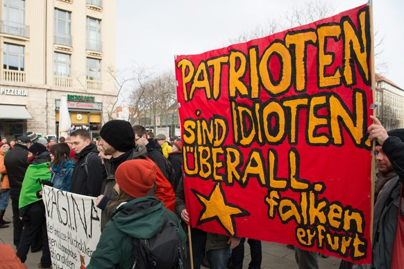 epa04581073 Participants of a leftist counterdemonstration hold a banner reading: 'Patriots are Idiots anywhere' as they gather in Erfurt, Germany, 24 January 2015. They were protesting against the first rally of the 'Pegada' (Patriotic Europeans against the Americanisation of the Occident) movement on the Cathedral Square in Erfurt. 'Pegada' - according to media reports - separates itself from the 'Pegida' (Patriotic Europeans against the Islamization of the West) claiming that not 'Islamization' is the problem but the 'dominating Americanization', with the USA and Israel's influence on media, monetary and finance policies. Reportedly 'Pegada' is supported by groups close to the extreme-right wing spectrum.  EPA/SEBASTIAN KAHNERT