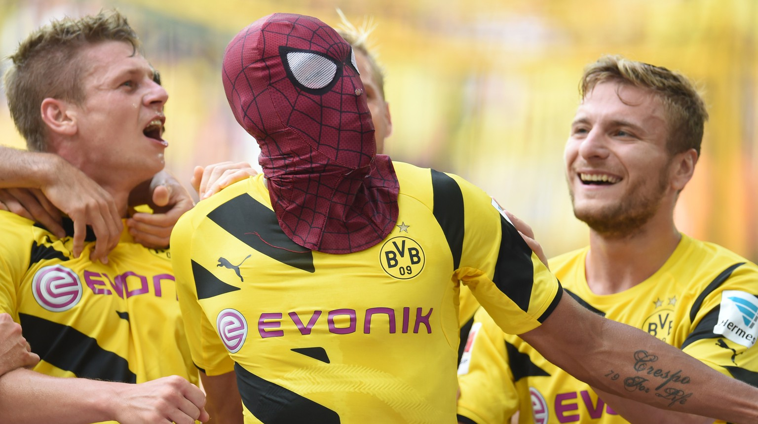 Dortmund's Italian striker Circo Immobile (R), Dortmund's Polish defender Lukasz Piszczek (L) celebrate after Dortmund's Gabonese striker Pierre-Emerick Aubameyang, who put on a Spiderman mark, scored the 2-0 goal during the German Supercup football match Borussia Dortmund vs Bayern Munich in the German city of Dortmund on August 13, 2014. AFP PHOTO / PATRIK STOLLARZ