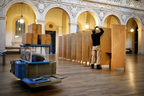 A worker prepares voting booths at a polling station in Lyon, central France, Saturday, April 22, 2017. The two-round presidential election will take place on April 23 and May 7. (AP Photo/Laurent Cipriani)
