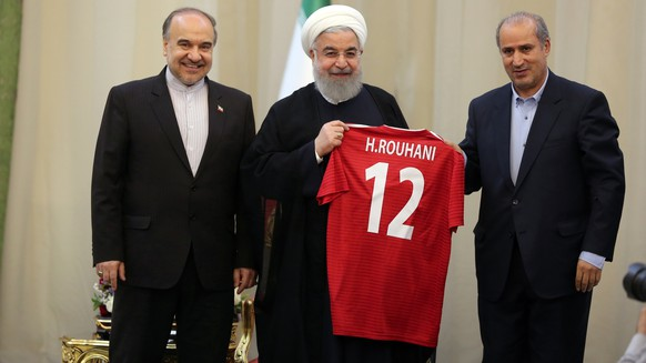 epa06752452 A handout photo made available by the Presidential office shows Iranian President Hassan Rouhani (C) poses with  the team's away jersey, in the presence of Iranian Football Federation President Mehdi Taj (R) and Iran's Minister of Sport and Youth Masoud Soltanifar (L) during a ceremony to bid farewell for the Iranian national team in Tehran, Iran, 20 May 2018. Iran national team will leave Tehran on 21 May to start a training camp abroad ahead of the 2018 FIFA World Cup finals in Russia.  EPA/PRESIDENTIAL OFFICE HANDOUT  HANDOUT EDITORIAL USE ONLY/NO SALES
