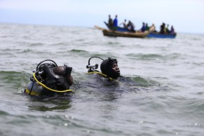 Members of the Uganda Police Marine Unit participate in a rescue operation after a boat carrying mostly Congolese refugees capsized in Lake Albert near Ntoroko southwest of Uganda's capital Kampala, March 23, 2014. According to the Uganda Police rescue team, a total of 25 bodies of mostly children have been retrieved, 45 rescued with hundreds more feared dead. The refugees were returning to DR Congo from Kyangwali refugee resettlement camp after relative peace returning to DR Congo in the recent weeks. REUTERS/Edward Echwalu (UGANDA - Tags: SOCIETY)