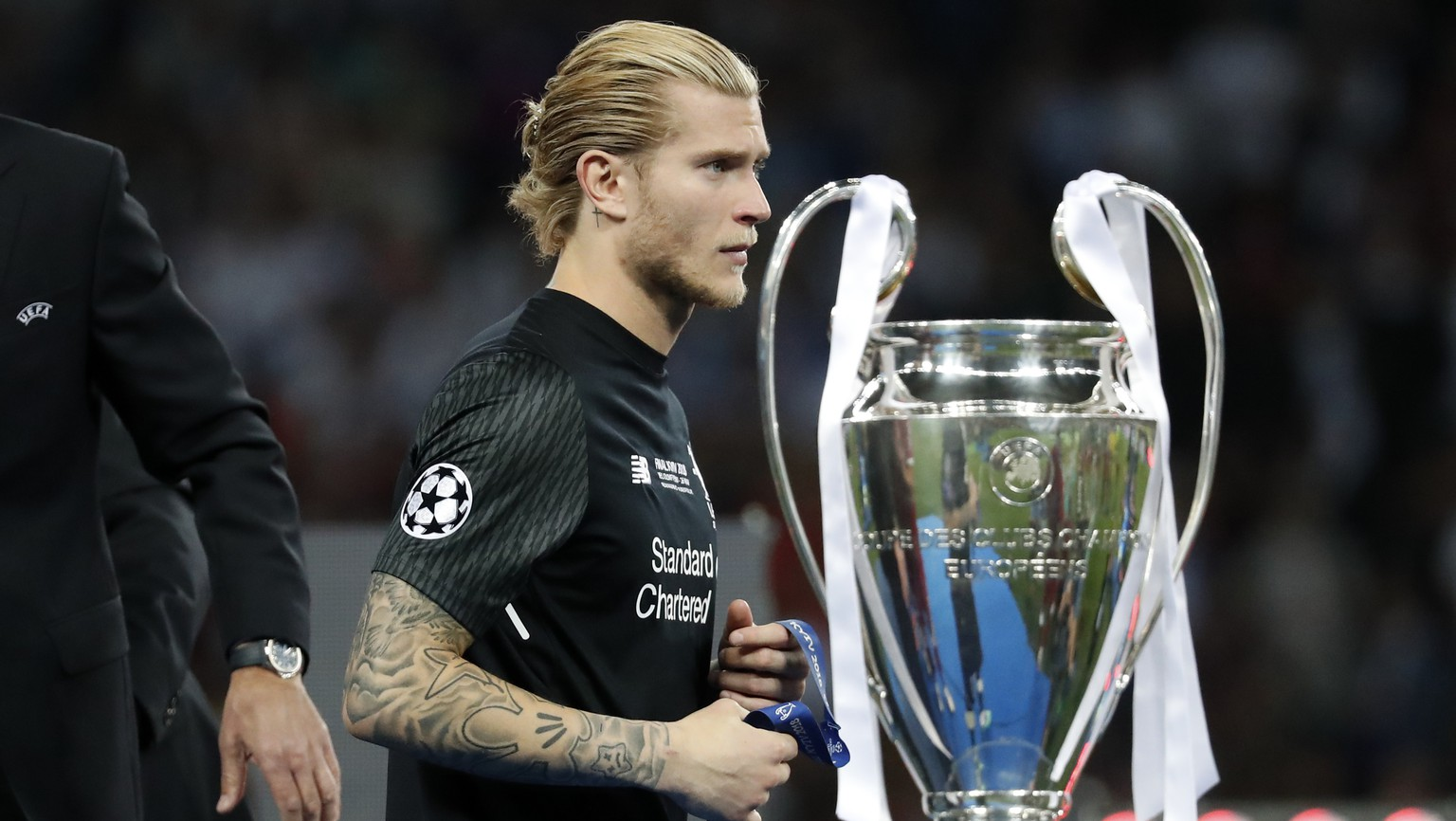 Liverpool goalkeeper Loris Karius walks past the trophy after the Champions League Final soccer match between Real Madrid and Liverpool at the Olimpiyskiy Stadium in Kiev, Ukraine, Saturday, May 26, 2018. Real Madrid won 3-1. (AP Photo/Pavel Golovkin)