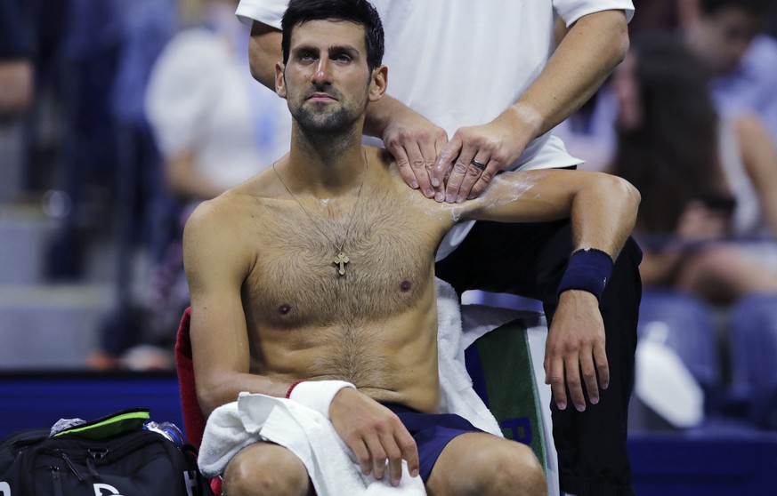 Novak Djokovic, of Serbia, receives treatment from a trainer during his match against Juan Ignacio Londero, of Argentina, during the second round of the U.S. Open tennis tournament in New York, Wednesday, Aug. 28, 2019. (AP Photo/Charles Krupa) Novak Djokovic