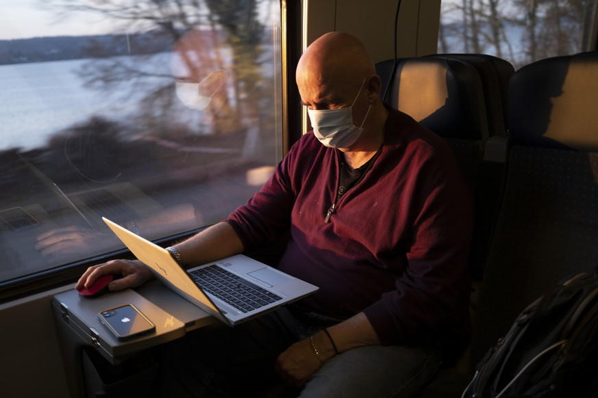 Passenger wearing protective mask works on a laptop as he rides a SBB CFF FFS train in front of the Bielersee  during the coronavirus disease (COVID-19) outbreak, in Neuchatel, Switzerland, Tuesday, March 23, 2021. Switzerland as many countries in Europe impose coronavirus restrictions to fight against the spread of coronavirus COVID-19. (KEYSTONE/Laurent Gillieron)