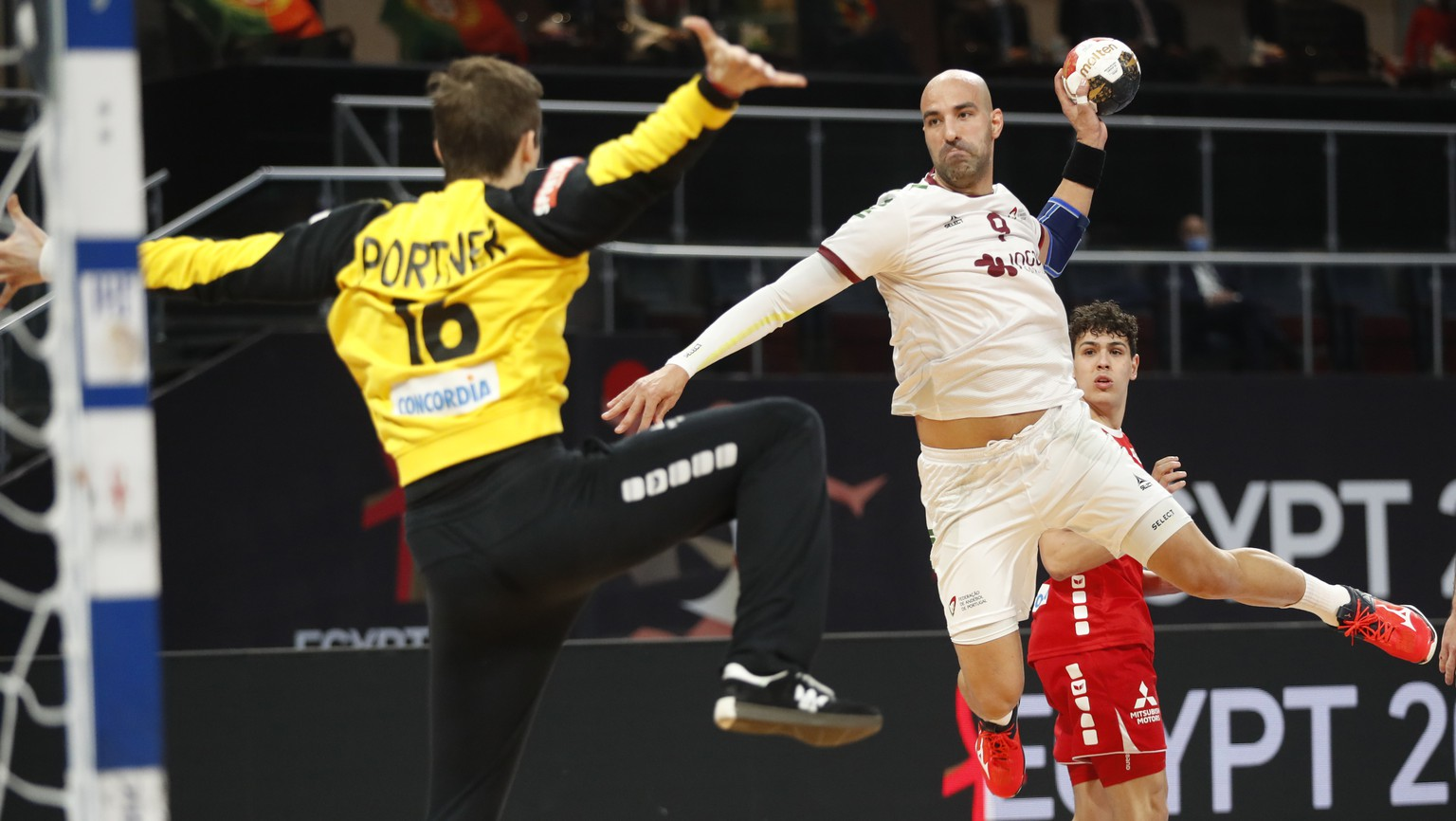 Portugal's Joao Ferraztakes a shoot as Switzerland's goal keeper Nikola Portner in action during the World Handball Championship between Switzerland and Portugal in Cairo, Egypt, Friday, Jan. 22, 2021. (AP Photo/Petr David Josek, Pool)