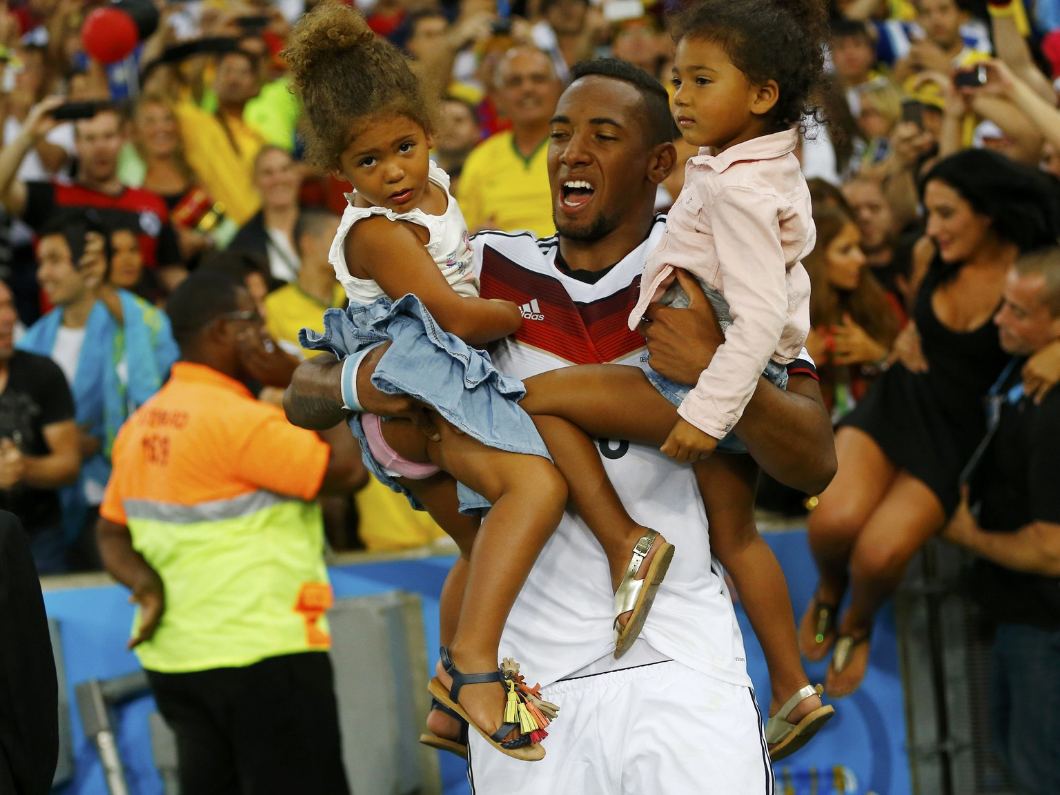 Germany's Jerome Boateng carries his children as he celebrates their win against Argentina in their 2014 World Cup final at the Maracana stadium in Rio de Janeiro July 13, 2014. REUTERS/Darren Staples (BRAZIL  - Tags: SOCCER SPORT WORLD CUP)