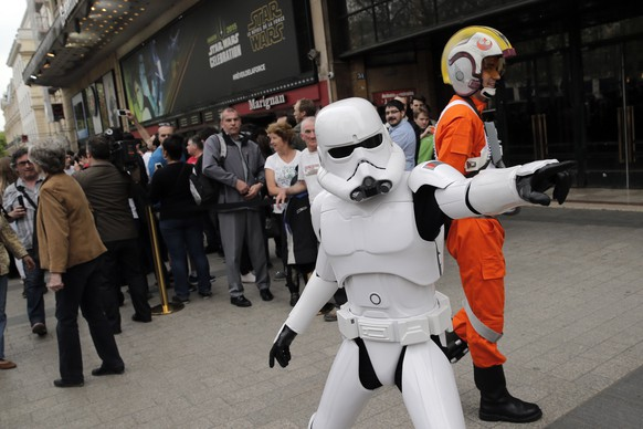 A man dressed as a Stormtrooper poses for photographers next to people queuing to attend the steaming of Star Wars Celebration from the Anaheim Convention Center in California, in Paris, France, Thursday, April 16, 2015. Star Wars Celebration is a fan gathering to celebrate the release of a Star Wars franchise movie , panel discussions, and exclusive reveals. (AP Photo/Christophe Ena)