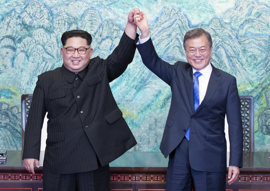 epa06696286 North Korean leader Kim Jong-Un (L) and South Korean President Moon Jae-In (R) join hands after signing a document at the Joint Security Area (JSA) on the Demilitarized Zone (DMZ) in the border village of Panmunjom in Paju, South Korea, 27 April 2018. South Korean President Moon Jae-in and North Korean leader Kim Jong-un are meeting at the Peace House in Panmunjom for an inter-Korean summit. The event marks the first time a North Korean leader has crossed the border into South Korea since the end of hostilities during the Korean War.  EPA/KOREA SUMMIT PRESS / POOL