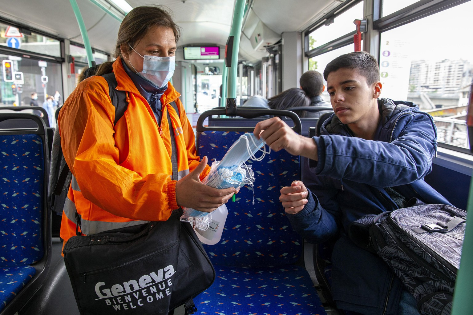 epa08417813 A member staff of the Transports publics genevois, TPG, (Geneva Public Transport), distributes protective face masks as a preventive mesure against the spread the coronavirus COVID-19 to passengers, in Geneva, Switzerland, 12 May 2020.  In Switzerland since 11 May, the Swiss authorities lifted second part of the lockdown. Classroom teaching at primary and lower secondary schools will again be permitted. Shops, markets, museums, libraries and restaurants reopen under strict compliance with precautionary measures as a precaution against the spread of the coronavirus COVID-19.  EPA/SALVATORE DI NOLFI