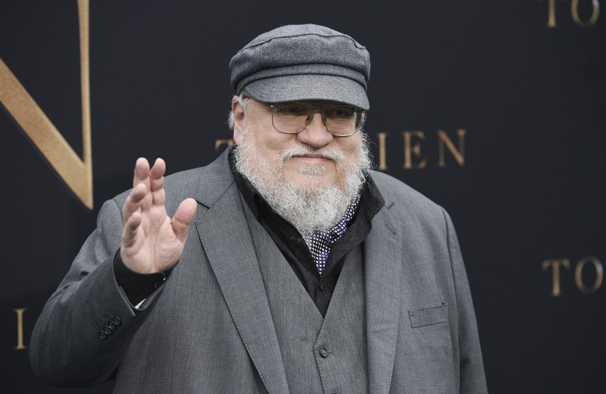 Author George R.R. Martin waves to photographers at the premiere of the film