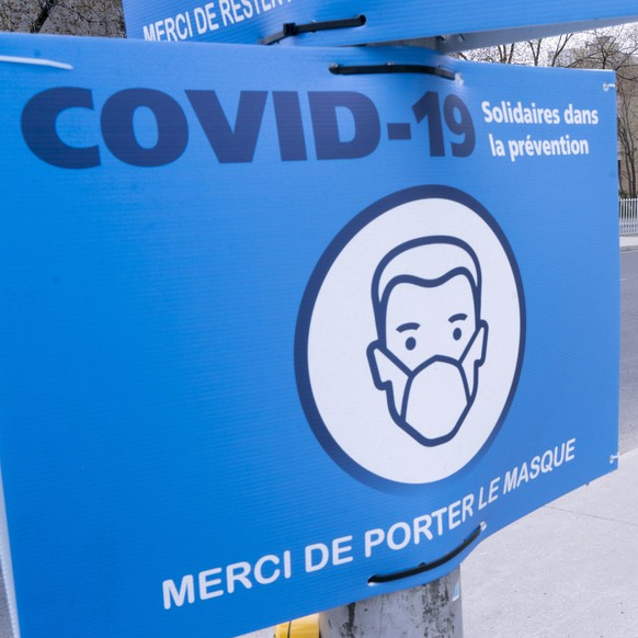 A sign asks Montrealers to voluntarily wear a protective face mask during the COVID-19 pandemic in Montreal, on Friday, May 15, 2020. (Paul Chiasson/The Canadian Press via AP)