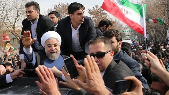 epa04603235 A handout picture made available by the presidential official website shows Iranian President Hassan Rowhani (L) waving to supporters in the city of Isfahan, central Iran, 04 February 2015. According to media reports, Rowhani said differences with the West over the disputed nuclear program are gradually decreasing and that 'both sides are approaching a good common point'.‬  EPA/PRESIDENTIAL OFFICIAL WEBSITE/HANDOUT  HANDOUT EDITORIAL USE ONLY/NO SALES
